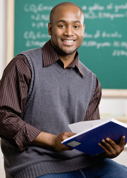 teacher with book in hand smiling