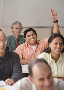 adult student smiling and raising hand to answer question