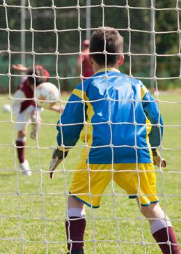 boy kicking soccer ball at goalie