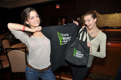 Two teenage girls posing with Young Women on the Move bag and t-shirt