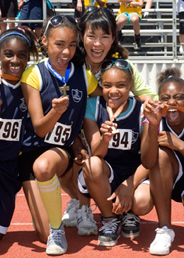 Elementary school girl's track and field team happily displaying their medals
