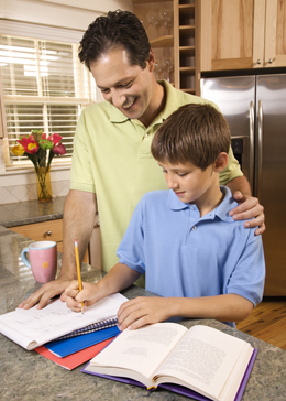 Smiling dad looking over the should of son doing homework at the kitchen counter