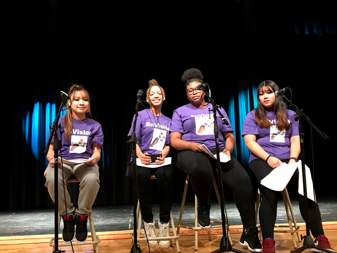 Four female students sit on stage with microphones at the Envision Conference