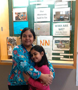 Parent Naghma hugging her daughter at the school while she volunteers in the building