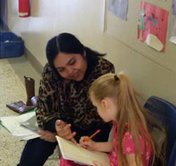 Parent Naghma working on reading with a student in grade 1 at John A. Leslie