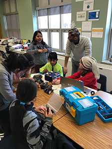 Parent Roy working with a group of students at a table helping them to build a robot at a after school club.