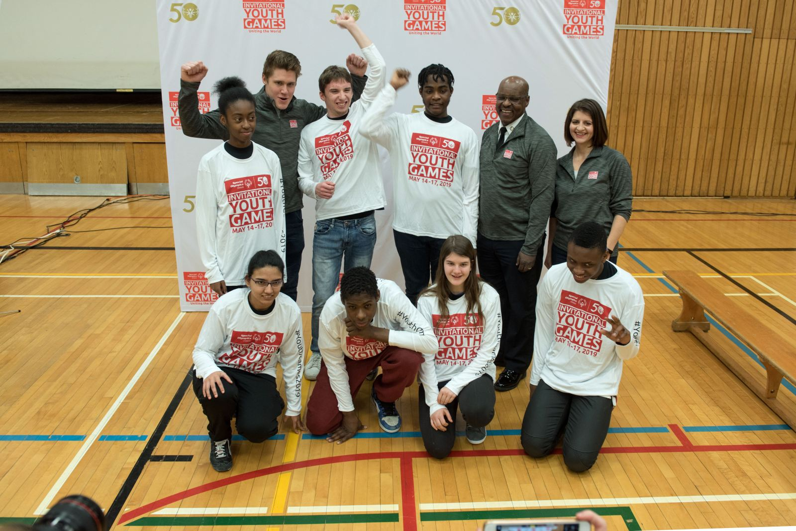 7 Students and 3 adults posing in front of a branded backdrop for the Invitational Youth Games