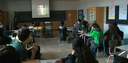 Students wearing green shirt and watching a movie in a class