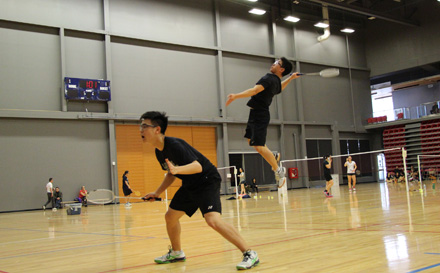 A doubles team reach high to attack at the City Championships game