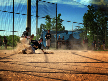 East York athlete slides into home base as the ball soars over from the field inches away from the back catcher's mitt.