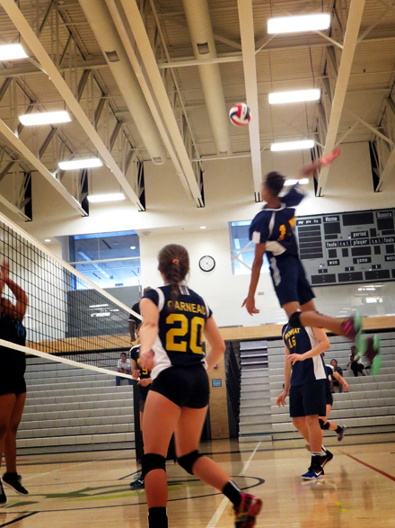 A boy from Sir Oliver Mowat soars above his teammates to spike the ball down against his opponents.