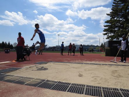 A competitor leaps into the sand pit during his attempt at the running long jump event.