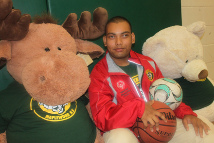 Antik Neer sits in his school gym at Maplewood HS surrounded by the mascots.