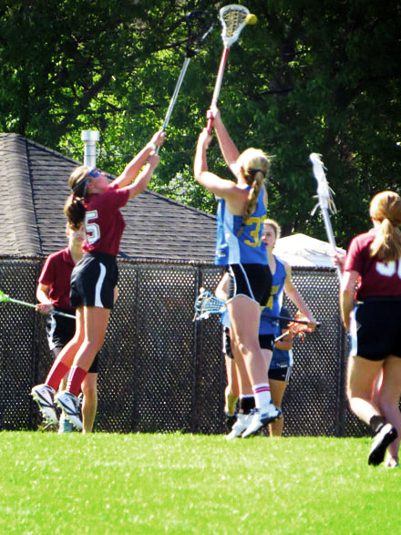 Female Lacrosse players from opposing teams reach with their sticks towards a flying ball.