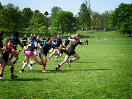 A girl breaks free from the pack in the rugby game trying to score in the end zone.