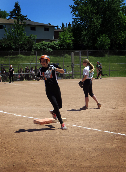 Martingrove batter jogs through first base smiling as her ball is caught and she is pronounced 'out'.