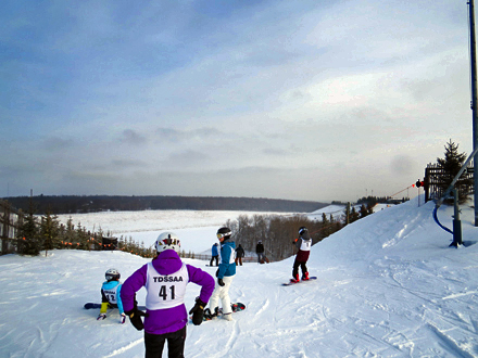 Snowboarders survey the conditions before heading down the hill at Mount St. Louis Moonstone.