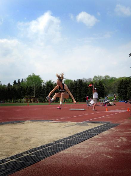 A female athlete smiles as she flies through the air in the triple jump event.