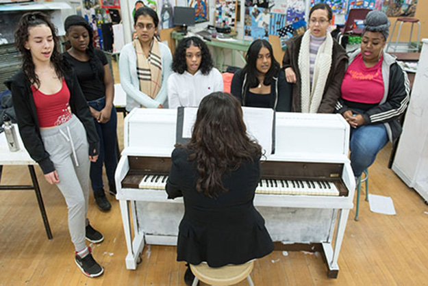 A teacher sits at a piano while seven students stand around it singing