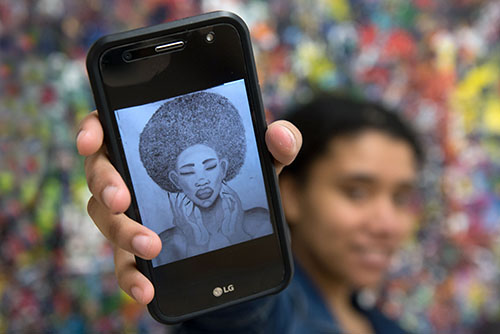 A student holds up a phone with an image of Black woman on it
