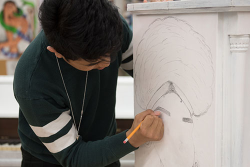A student sketches an outline of a woman with an afro