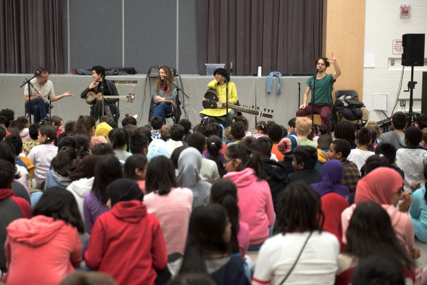 a large group of students watch a performance by Kune who is at the front of the gymnasium with instruments and microphones
