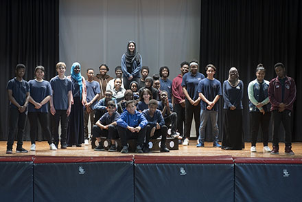The student cast of 27 students poses for the camera on the school's stage.