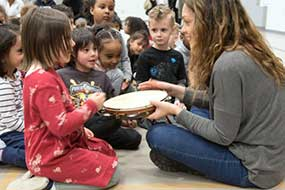 A group of young students interact with a musician and a tambourine