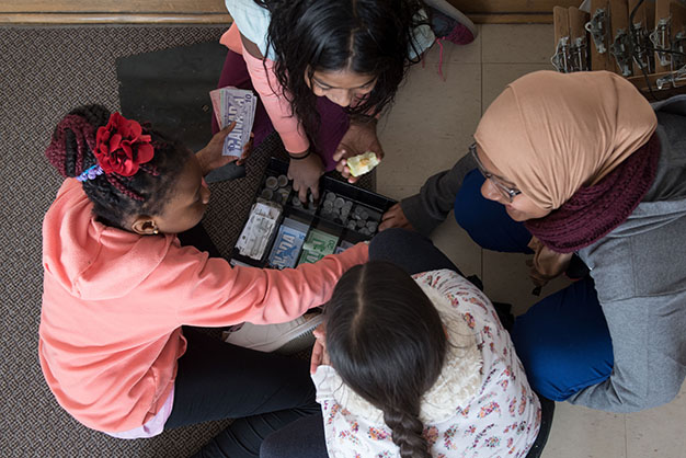 A group of elementary students us play money to practice a math lesson in class