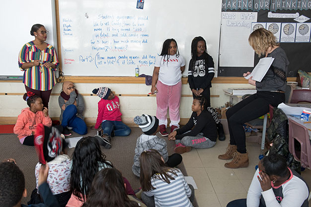 A teacher is reading from a math book in front of a class of elementary students